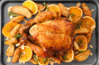 Roasted turkey with slices of orange and potatoes on baking sheet
