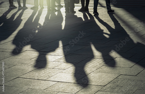 Shadows and silhouettes of people at a city during sunset