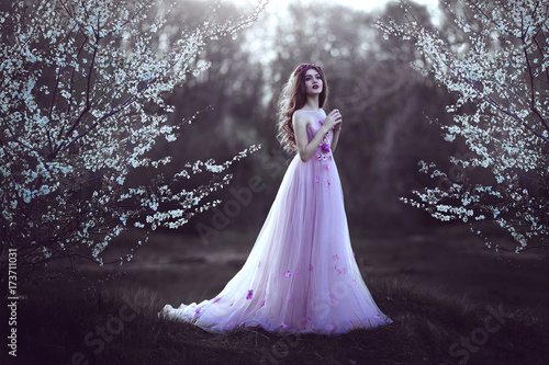 Obraz na plátně  Beautiful Romantic Girl with long hair in pink dress near flowering tree