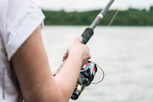 Plakat kobiece ręce trzyma wędkę i przekręcić uchwyt kołowrotku. Niewielka głębokość pola, nieostrość