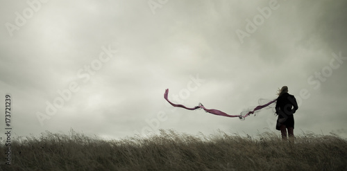 Photo Woman standing alone in harsh weather with dramatic sky