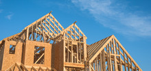 Close-up Of Gables Roof On Stick Built Home Under Construction And Blue Sky In Humble, Texas, USA. New Build Roof With Wooden Truss, Post And Beam Framework. Timber Frame House, Real Estate. Panorama