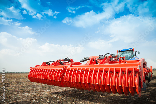 Fotografia, Obraz Modern tractor in the field with complex for the plowing of soil.