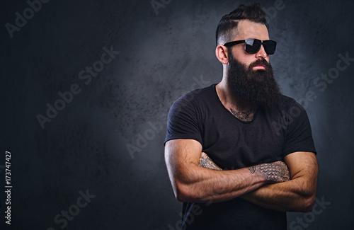 Obraz na płótnie A man in a black shirt with tattoos on his arms.