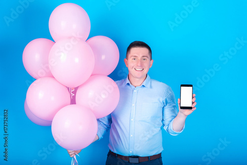 Young handsome smiling man in blue shirt holding pink air