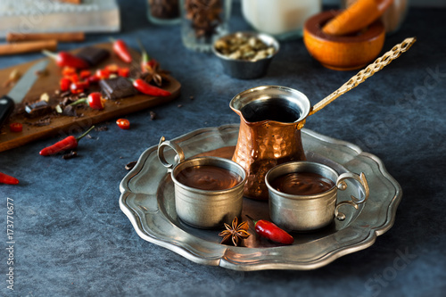 Spoed Foto op Canvas Chocolade Spicy Spanish Hot Chocolate in Metal Cups with Ingredients on Kitchen Counter