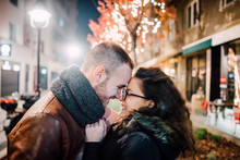 Couple Having A Romantic Moment In Front Of The Decorated Tree