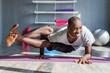 Handsome yogi smiling while doing an intense yoga pose - ashtavakrasana in a bright fitness studio
