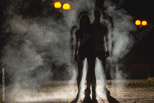 Fotografia  The couple stand on the dark alley on the fume background