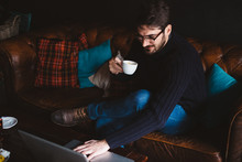 Handsome Man Working On His Computer While Drinking Coffee