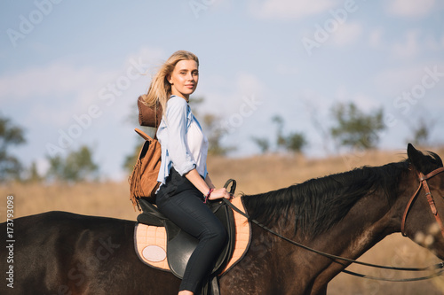 Poster Equitation Beautiful young cowgirl riding her horse in field