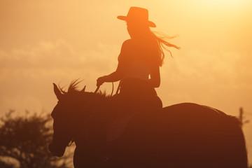 Zmierzch sylwetka młody cowgirl jedzie jej konia