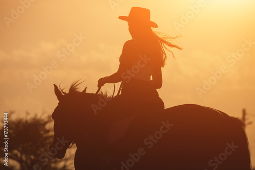 Poster Horseback riding Sunset silhouette of young cowgirl riding her horse