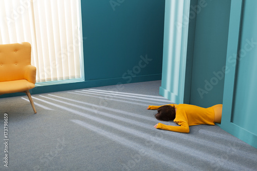 woman with yellow sweater lying on carpet