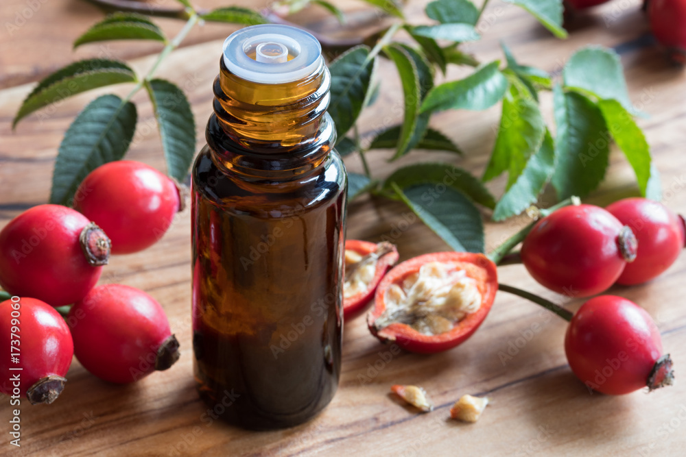 Fototapety, obrazy: A bottle of rosehip seed oil on a wooden table