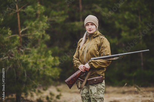 Female hunter in camouflage clothes ready to hunt, holding gun and walking in forest.