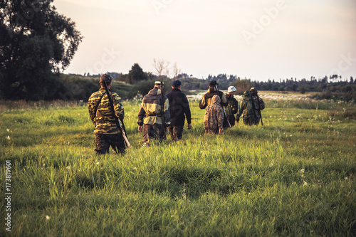 Foto op Canvas Jacht Hunting scene with group of men hunters going through tall grass on rural field at sunset during hunting season