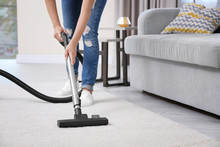 Woman Cleaning Carpet With Vac...