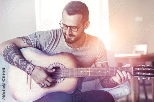 Fototapeta przystojny mężczyzna gra na gitarze akustycznej