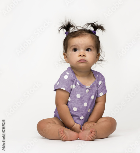 00af9d2f1 Sweet, serious baby girl sitting in polka dot onesie on white background