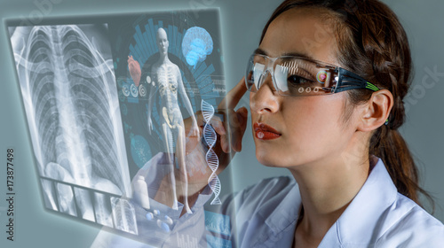 Young female doctor looking at hologram screen Canvas Print