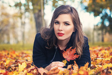 Cute Girl Outdoors. Beautiful Woman Fashion Model With Autumn Leaves