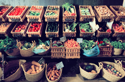 Poster Cuisine vegetables and fruits in wicker baskets in greengrocery