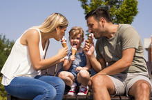 Parents And Kid Eating Ice Cream And Having Fun Outside