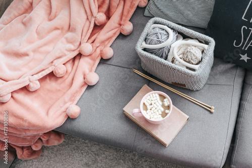 Obraz Knitting, book, cocoa and blanket on the sofa - fototapety do salonu