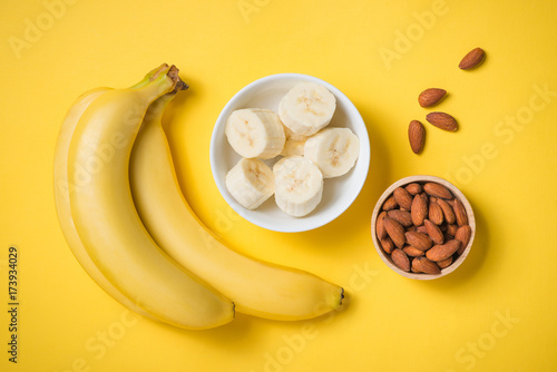 Fresh made banana smoothie in a glass on yellow background