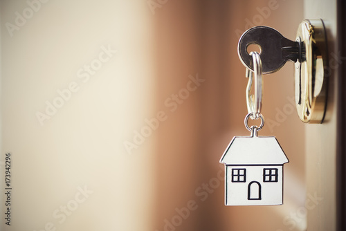 Cuadros en Lienzo  House key on a house shaped silver keyring in the lock of a door