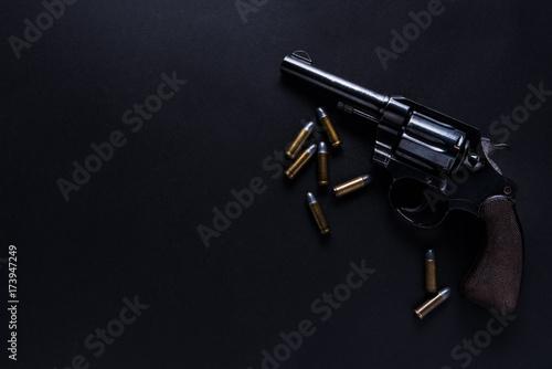Fotografiet gun with bullets on black background