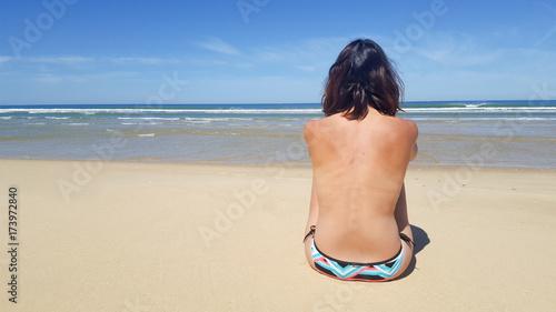 Plakat Tylny widok szczęśliwy dziewczyny odzieży bikini przy morze plażą i spojrzenie krajobraz