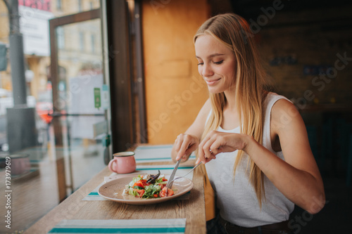 Staande foto Kruidenierswinkel Portrait of attractive caucasian smiling woman eating salad