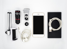 Flat Lay (Top View) Image Of Accessories (Tripod Phone Holder, Universal Clamp Camera Lens, Earphone, Power Bank, USB Charger Cable) Around Smartphone On White Background
