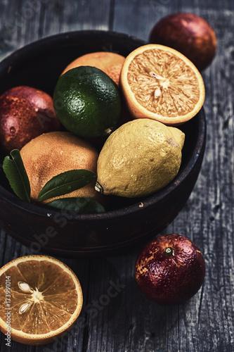 owoce-cytrusowe-w-drewnianej-misce-na-ciemnym-tle