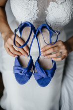 Bride Holds The Wedding Shoes
