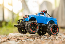 Blue RC Off-road Truck Car (Radio-controlled) Standing On The Rock And Terrain Sand Dune. This Toy Has Some Dust From Children Playing.