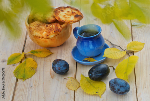 jesienne-zdjecie-z-herbata-ciastkami-sliwkami-i-opadajacymi-liscmi