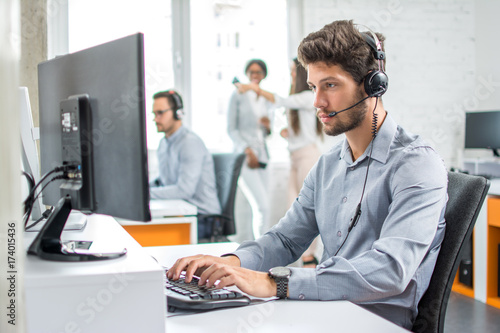Cuadros en Lienzo  Young handsome male customer support phone operator with headset working in call center