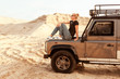 Woman dreams of sitting on the hood of a car in the desert sands, she travels on off-road.