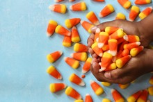 Child's Hands Holding Halloween Candy Corn, Selective Focus