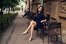 Lovely Young Brunette Woman, Wearing Black Skater Dress With Shortened Sleeves, Sitting With Her Legs Crossed In Chair At Table Of Outdoor Cafe. Gorgeous Female Model Posing Beside Antique Building.
