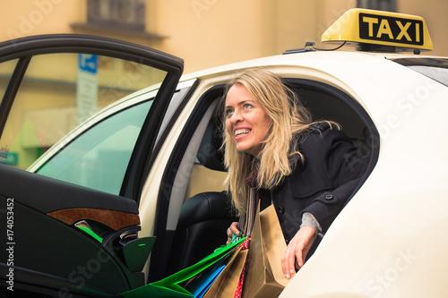 Plakat Młoda kobieta dostaje z taksówki przewożących torby na zakupy w ręce