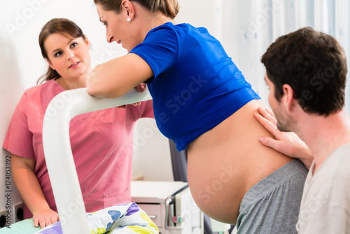 Fotomural Woman laboring in delivery room with nurse and husband before birth