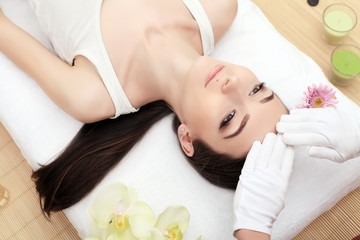 Obraz na płótnie Canvas people, beauty, spa, healthy lifestyle and relaxation concept - close up of beautiful young woman lying with closed eyes and having face or head massage in spa