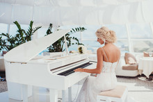 He Bride's Portrait In A Classical White Dress. The Young Fair-haired Girl Marries. The Girl Plays White Grand Piano, The Stylish Bride