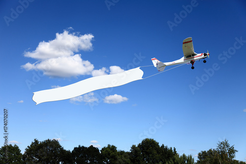 Obraz Reklama lotnicza, samolot ciągnie transparent. - fototapety do salonu