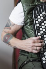 Closeup Of A Tattooed Arm Playing The Accordion