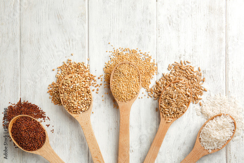 Different grains in spoons on wooden background